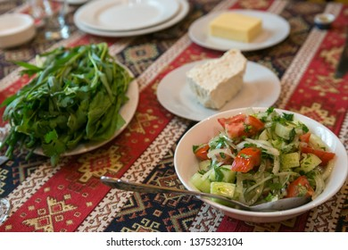 Healthy salad with seasonal vegetables, and starters on a table with colorful napkin