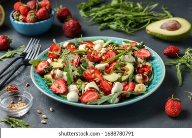 Healthy salad with strawberries, avocado, arugula and mozzarella, dressed with olive oil and balsamic dressing in a blue plate on a dark background