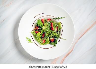 healthy salad with strawberriesa and arugula