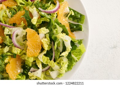 healthy salad from tangerines and lettuce with red onions on a bright background, close up, high angle view from above
