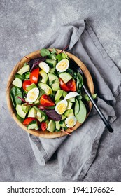 Healthy salad with tomatoes, avocado, cucumber and eggs on wooden plate.