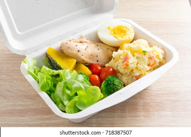 Healthy salad with tomatoes, chicken, egg, mash potato, and mixed greens (Broccoli, pumpkin) on wooden background. Healthy food.