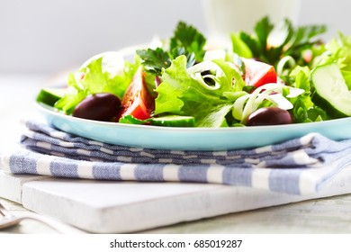 Healthy salad with tomatoes, cucumber, red onion, olives and lettuce on wooden background. Concept for tasty and healthy meal.