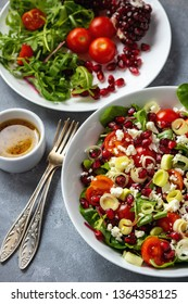 Healthy salad with tomatoes, feta, pomegranate seeds and leek.