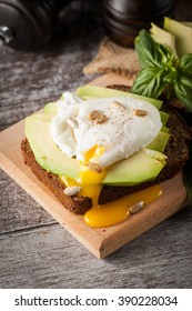 Healthy sandwich with avocado and poached eggs. Healthy food and diet concept.