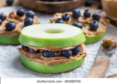 Healthy sandwich. Green apple rounds with peanut butter and and blueberries on wooden table, horizontal