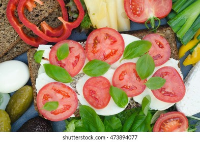 healthy sandwich with mozzarella, tomato and basil on table