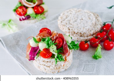 Healthy sandwich with rice cake, lettuce, mozzarella, cherry tomatoes and prosciutto