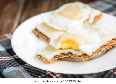 Healthy sandwiches with soft cheese and egg on crisp rye bread on dark wooden background. Breakfast or snack.