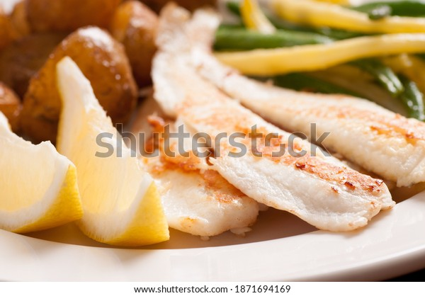 healthy sauteed tilapia fish fillets with beans and fingerling potaotes and lemon