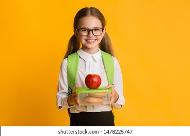 Healthy School Lunch. Adorable Elementary Student Girl Holding Lunchbox With Sandwiches And Apple Over Yellow Background. Copy Space
