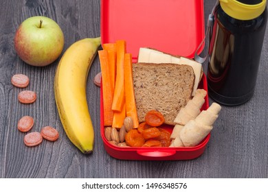 Healthy school lunch box with sandwich, apple, banana, almonds, dry fruits, water, natural candies, carrot, biscuits.