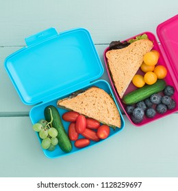 Healthy school lunch boxes for children with sandwich and fresh vegetables and fruit
