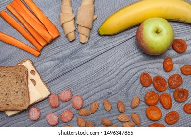 Healthy school lunch with sandwich with cheese, apple, banana, almonds, dry fruits, water, natural candies, carrot, biscuits on wooden background. Copy space, flat lay, top view.