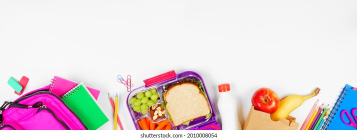 Healthy school lunch with school supplies. Top view bottom border on a white banner background. Back to School concept.