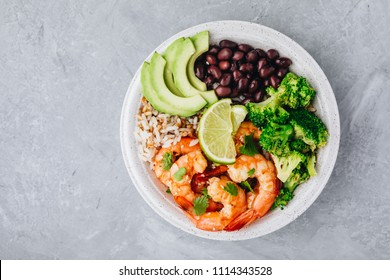 Healthy seafood lunch. Spicy Shrimp Burrito Buddha Bowl with wild rice, broccoli, black beans and avocado