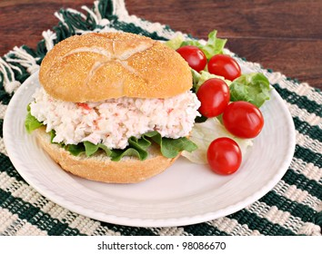 Healthy seafood salad sandwich on a hard roll with a side salad and tomatoes.