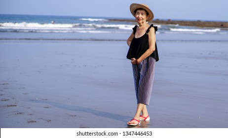Healthy senior asian woman enjoying a morning walk by the  beach.