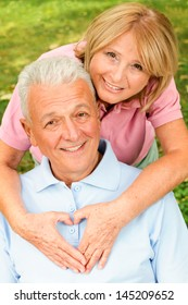 Healthy senior couple in park. Female showing heart symbol on his chests.