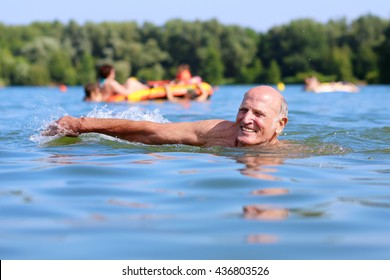 Healthy senior man swimming in the lake or river. Happy elderly man enjoying active summer vacation. Sportive lifestyle. Active retirement concept.