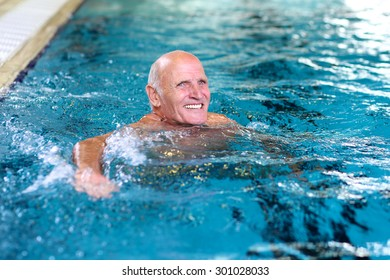 Healthy senior man swimming in the pool. Happy pensioner enjoying sportive lifestyle. Active retirement concept.