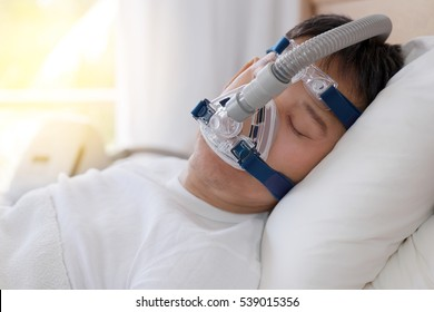 Healthy senior man wearing cpap mask sleeping smoothly all night on his back without snoring,side view with backlit.Obstructive sleep apnea therapy.
