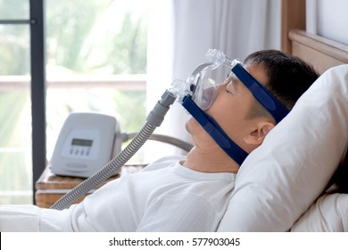 Healthy senior man wearing cpap mask sleeping smoothly on his back without snoring during day break,side view with backlit.Obstructive sleep apnea therapy.