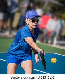 Healthy senior woman athelete hits a Pickleball volley