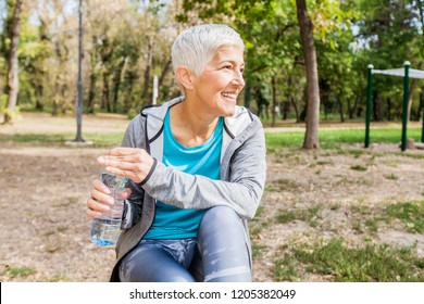 Healthy Senior Woman Relax And Hold Bottle Of Water After Workout At Outdoor Fitness Park