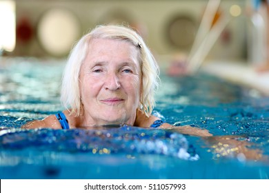 Healthy senior woman swimming in the pool. Happy pensioner enjoying sportive lifestyle. Active retirement concept.