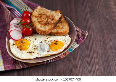 Healthy simple breakfast with bread toast, fried eggs and vegetables. Selective focus, closeup view