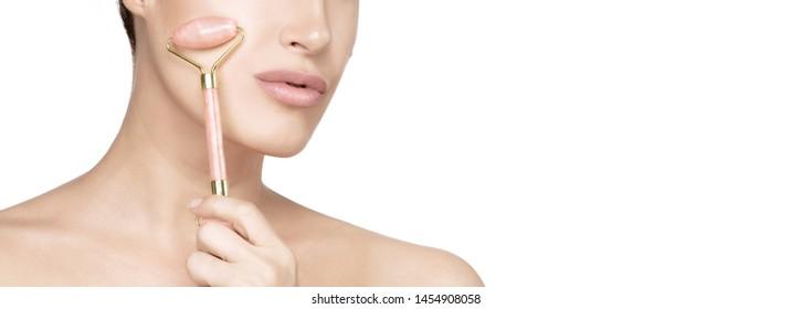 Gesunde Hautfrau, die eine rosarote Quarzwalze auf ihrer flachen Haut verwendet. Schönheit Gesicht, Nahaufnahme. Konzept der Gesichtsbehandlungen mit Schmucksteinen. Bannerpanorama einzeln auf Weiß mit Kopienraum
