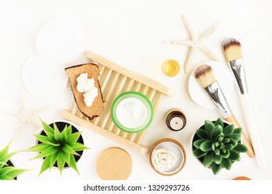 Healthy skincare facial treatment preparation, vegan beauty cosmetic products background. Facial moisturizer jar, green aloe plant, nourishing body butter. Spa at home, Top view white table.