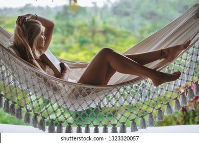 Healthy sleep in the open air at hammock. Sexy woman relaxing at luxury villa with beautiful view at the rice terraces Jatiluwih. Book you hotel for honeymoon at Bali, Ubud.