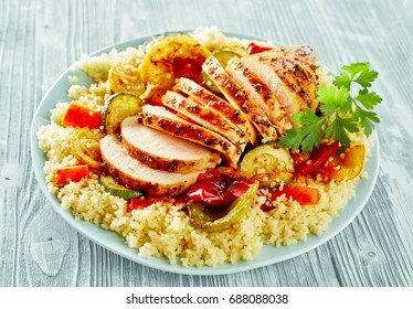 Healthy sliced lean grilled chicken breast on savory couscous with roasted vegetables including courgette, peppers and tomato served on a plate on a grey wood table