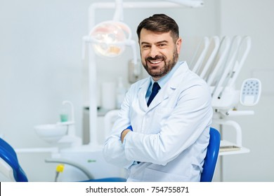 Healthy smile. Positive bearded dentist expressing cheer while standing in front of you and keeping arms in crossed position