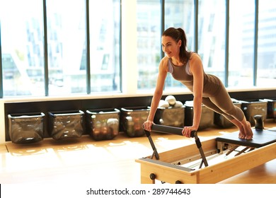 Healthy Smiling Brunette Woman Wearing Leotard and Practicing Pilates in Exercise Studio