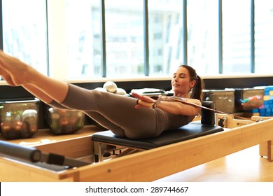 Healthy Smiling Brunette Woman Wearing Leotard Practicing Pilates in Bright Exercise Studio