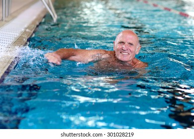 Healthy smiling senior man swimming in the pool. Happy pensioner enjoying sportive lifestyle. Active retirement concept.