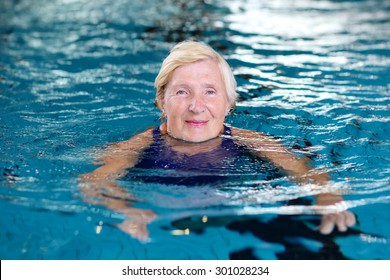 Healthy smiling senior woman swimming in the pool. Happy pensioner enjoying sportive lifestyle. Active retirement concept.