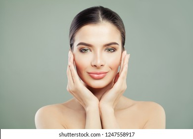 Healthy smiling woman with clear skin touching her hands her face