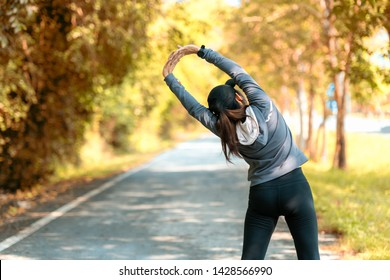 Healthy smiling woman warming up stretching her arms and looking away in the road outdoor. Asian runner woman workout before fitness and jogging session at the park. Healthy and Lifestyle Concept.