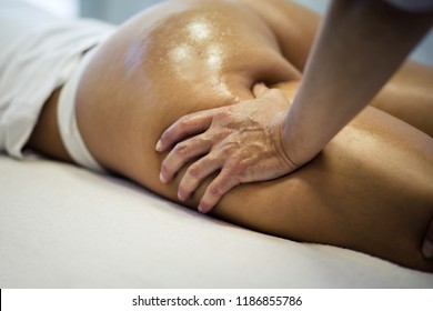 Healthy and smooth body. The masseur makes Anti-cellulite massage on the buttock and thighs of the patient. Close up.