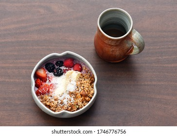 Healthy smoothie bowl with colorful mixed fruit and coffee in clay mug isolated on wooden background