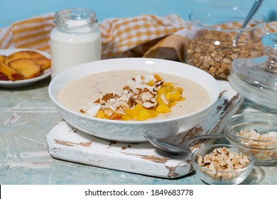 healthy smoothie bowl with mango, coconut and nuts for breakfast, horizontal