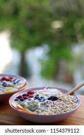Healthy smoothie bowls. Mango, peach and banana smoothie with various toppings granola, coconut flakes, chia seeds, kiwi, blueberries, raspberries, peach. Selective focus.