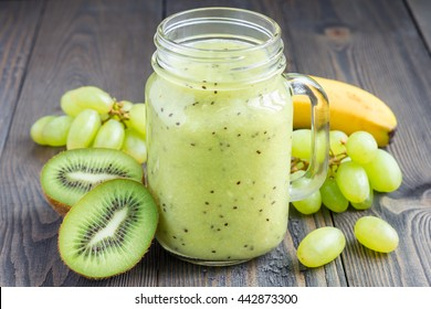 Healthy smoothie with kiwi, green grape, and banana in glass jar, horizontal