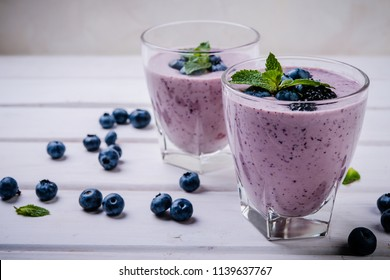 healthy smoothie or shake with fresh blueberries on a white wooden  background