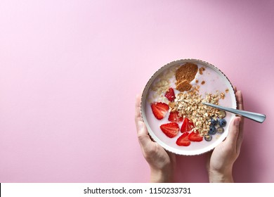 Healthy smoothie in white bowl with natural fruits, oat flakes and biscuits with woman's hands holding a bowl on pink background. Superfoods, natural detox, diet and healthy food. Flat lay