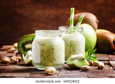 Healthy Smoothies from kiwi, banana, green apple and pistachios, vintage wooden background, selective focus